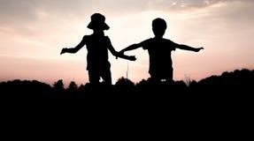 Konturer av barn som hoppar av en klippa på solnedgången Royaltyfri Fotografi