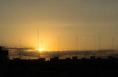 Konturer av byggnader och antenner in på solnedgången staden Royaltyfri Foto
