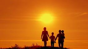 Konturer av den lyckliga familjen av fyra som går på solnedgången stock video