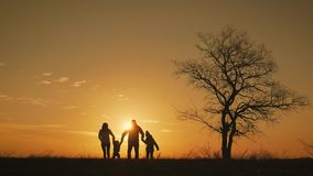 Konturer av den lyckliga familjen som g?r i ?ngen n?ra ett stort tr?d under solnedg?ng arkivfilmer