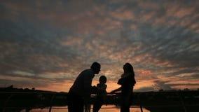 Konturer av den lyckliga familjen som tillsammans går på solnedgången stock video