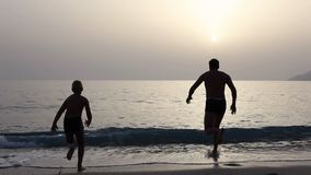 Konturer av dykning för sol för fadermanpojke som öser på solnedgånghavet stock video