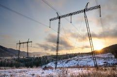 Konturer av elektricitetspyloner under en vintersolnedgång royaltyfria bilder