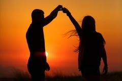 Konturer av ett älska par på solnedgången Begreppet av förälskelse och romans arkivbild