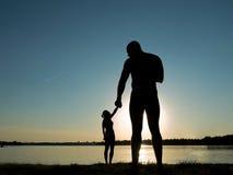 Konturer av ett älska par på stranden Solnedgång på stranden Jätten och behandla som ett barn Arkivfoton