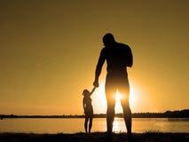 Konturer av ett älska par på stranden Solnedgång på stranden Jätten och behandla som ett barn Royaltyfri Fotografi