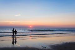 Konturer av ett par som tycker om solnedgången på Atlanticet Ocean Royaltyfri Fotografi