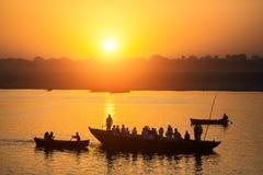 Konturer av fartyg med vallfärdar under solnedgång på heliga Ganges River, Varanasi royaltyfria foton