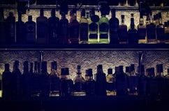 Konturer av flaskor med alkoholtempel av skuld på en hylla i en nattklubbstång royaltyfri bild