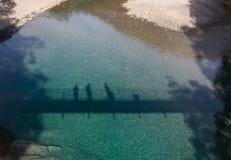 Konturer av folk på en upphängningbro Fotografering för Bildbyråer