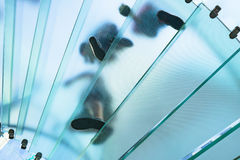 Konturer av folk som går på en glass spiraltrappuppgång Royaltyfri Fotografi