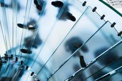 Konturer av folk som går på en glass spiraltrappuppgång Royaltyfria Foton