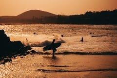 Konturer av folk som simmar och surfar på stranden Royaltyfria Bilder