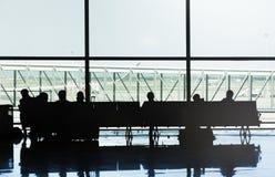 Konturer av folk som sitter p? stolarna av en flygplats som v?ntar p? deras flyg royaltyfri fotografi