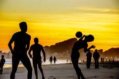 Konturer av folk som spelar strandfotboll på bakgrunden av den härliga guld- solnedgången på den Copacabana stranden, Rio de Jane royaltyfri foto