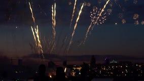 Konturer av folk under fyrverkerier i bakgrunden av en nattstad långsam rörelse stock video