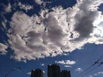Konturer av högväxta byggnader under ett stort vitt moln royaltyfria bilder