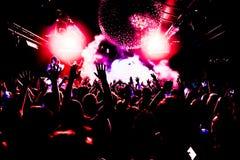 Konturer av konserten tränger ihop framme av ljusa etappljus med konfettier Royaltyfria Foton