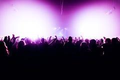 Konturer av konserten tränger ihop framme av ljusa etappljus med konfettier Royaltyfri Foto