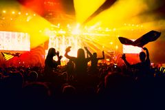 Konturer av konserten tränger ihop framme av ljusa etappljus Royaltyfri Foto
