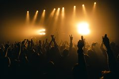 Konturer av konserten tränger ihop framme av ljusa etappljus Oigenkännligt folk i folkmassa Kopieringsutrymmebakgrund Folkmassa a royaltyfri bild