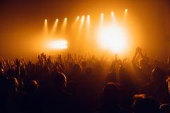 Konturer av konserten tränger ihop framme av ljusa etappljus Oigenkännligt folk i folkmassa Kopieringsutrymmebakgrund Folkmassa a fotografering för bildbyråer