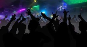 Konturer av konserten tränger ihop med händer som lyfts på ett musikdisko Royaltyfri Fotografi