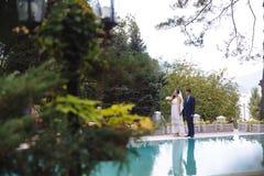 Konturer av nygifta personerna reflekteras i vattnet, paren är kringresande längs det gröna territoriet av hotellet royaltyfri fotografi