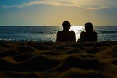 Konturer av par, en man och en kvinna sitter på en sandig strand och ser solnedgången på havet på en semester arkivbilder