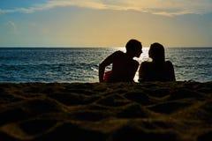 Konturer av par, en man och en kvinna sitter på en sandig strand och ser solnedgången på havet på en semester royaltyfri foto