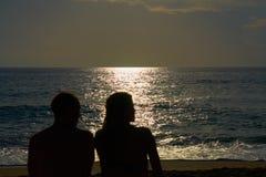 Konturer av par, en man och en kvinna sitter på en sandig strand och ser solnedgången på havet på en semester fotografering för bildbyråer