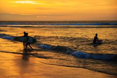 Konturer av par av unga surfare med surfingbrädor som går på stranden i solnedgång royaltyfri bild