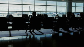 Konturer av passagerare i flygplatsterminalen Sitta vänta på ett flyg på det stora fönstret var en trafikflygplan lager videofilmer