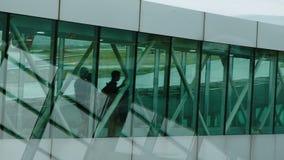 Konturer av passagerare passerar längs den genomskinliga korridoren stock video