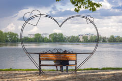 Konturer av pysen och flickan sitter på en bänk in för Royaltyfri Foto