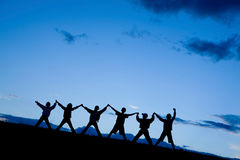 Konturer av sex barn som tillsammans hoppar Royaltyfri Fotografi