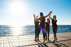 Konturer av sportive flickor som ger det highfive near havet på soluppgång Arkivbild