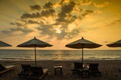Konturer av strandparaplyer solnedgång och himmel Arkivfoto