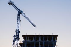Konturer av tornkranar mot aftonhimlen konstruktionshus under Arkivfoton