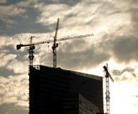 Konturer av tornkranar ovanför kontorsbyggnad arkivfoton