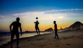 Konturer av tre män som spelar strandfotboll på bakgrunden av den härliga solnedgången på den Copacabana stranden, Rio de Janeiro arkivfoton