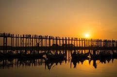 Konturer av turister i fartyg som beundrar bron för U Bein över Taungthaman sjön på solnedgången, i Amarapura, Mandalay Myanmar Royaltyfri Bild