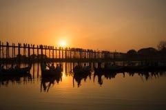 Konturer av turister i fartyg som beundrar bron för U Bein över Taungthaman sjön på solnedgången, i Amarapura, Mandalay Myanmar Royaltyfria Bilder