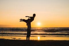 Konturer av två dansare som gör akrobatik på solnedgången arkivbilder