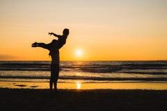 Konturer av två dansare som gör akrobatik på solnedgången arkivfoto