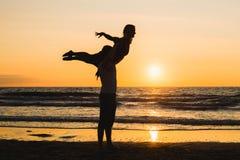 Konturer av två dansare som gör akrobatik på solnedgången arkivfoton