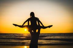 Konturer av två dansare som gör akrobatik på solnedgången arkivbild