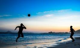 Konturer av två hoppa män som spelar strandfotboll på Copacabana, Rio de Janeiro royaltyfri fotografi