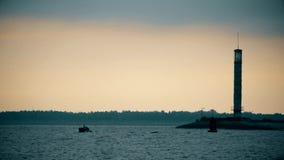 Konturer av två män i ett fartyg nära fyren på skymning lager videofilmer