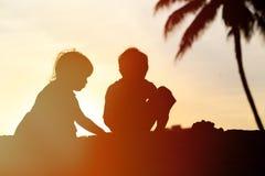 Konturer av två ungar spelar på solnedgångstranden Royaltyfri Foto